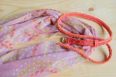Accesorios rosados de moda en el fondo de madera - bufanda, correa Fotografía de archivo libre de regalías
