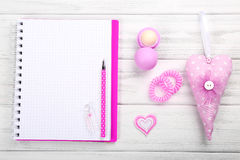 Accesorios rosados femeninos con el cuaderno en blanco en el backg de madera blanco Fotografía de archivo libre de regalías