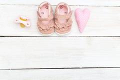 Accesorios rosados para los bebés en un fondo blanco de madera Co Fotografía de archivo libre de regalías