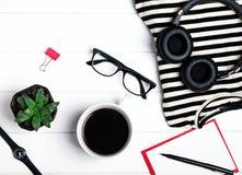 Accesorios y café del ` s de la mujer en la tabla de madera blanca, Imagen de archivo