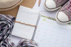Accesorios y calendario del viajero en el fondo de madera blanco VI Foto de archivo
