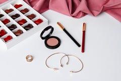Accesorios y chocolate decorativos de los cosméticos sobre el fondo blanco Fotografía de archivo libre de regalías