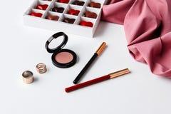 Accesorios y chocolate decorativos de los cosméticos sobre el fondo blanco Fotografía de archivo