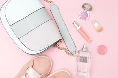 Accesorios y cosméticos femeninos del color rosado en un backgro rosado Imagen de archivo libre de regalías