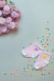 Accesorios y flores del bebé sobre fondo gris Imágenes de archivo libres de regalías