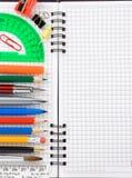Accesorios y fuentes de la escuela en el cuaderno Foto de archivo