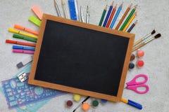 Accesorios y fuentes de la escuela: lápices, marcadores, pinturas, plumas, pizarra para las inscripciones en un fondo ligero De n Fotografía de archivo