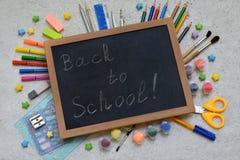 Accesorios y fuentes de la escuela: lápices, marcadores, pinturas, plumas, pizarra para las inscripciones en un fondo ligero De n Imágenes de archivo libres de regalías