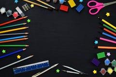 Accesorios y fuentes de la escuela: lápices, marcadores, pinturas, plumas, pizarra para las inscripciones en un fondo oscuro De n fotografía de archivo
