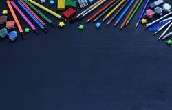 Accesorios y fuentes de la escuela: lápices, marcadores, pinturas, plumas, pizarra para las inscripciones en un fondo oscuro De n Imagenes de archivo