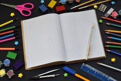 Accesorios y fuentes de la escuela: lápices, marcadores, pinturas, plumas, pizarra para las inscripciones en un fondo oscuro De n Imagen de archivo libre de regalías