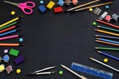 Accesorios y fuentes de la escuela: lápices, marcadores, pinturas, plumas, pizarra para las inscripciones en un fondo oscuro De n Foto de archivo