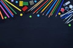 Accesorios y fuentes de la escuela: lápices, marcadores, pinturas, plumas, pizarra para las inscripciones en un fondo oscuro De n Fotos de archivo