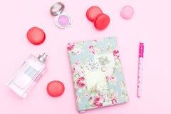 Accesorios y macarrones femeninos de la fresa en un fondo rosado Imagen de archivo libre de regalías
