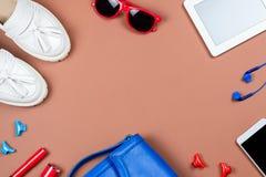 Accesorios y ropa de la mujer en colores rojos y azules en un fondo neutral Foto de archivo