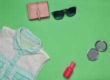 Accesorios y ropa de las mujeres en un fondo verde Camisa de los vaqueros, espejo, botella de perfume, gafas de sol, monedero Cop Foto de archivo