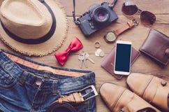 Accesorios y ropa para el viaje en un piso de madera Imágenes de archivo libres de regalías