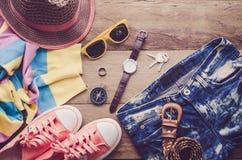 Accesorios y ropa para el viaje en un piso de madera Foto de archivo libre de regalías