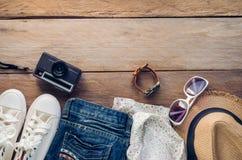 Accesorios y traje del viaje en piso de madera Foto de archivo