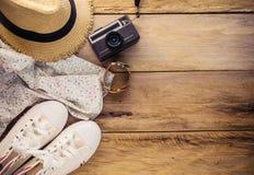 Accesorios y traje del viaje en piso de madera Imagenes de archivo