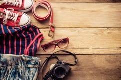 Accesorios y traje del viaje en piso de madera Fotos de archivo