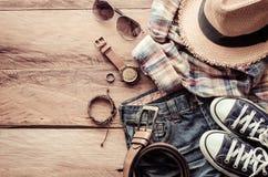 Accesorios y traje del viaje en piso de madera Imagen de archivo libre de regalías