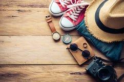 Accesorios y traje del viaje en piso de madera Imagen de archivo
