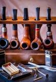 Accesorios y tubos de tabaco que fuman en un estante de tubo de madera Foto de archivo
