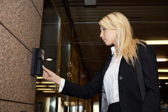 Access. Young businesswoman entering access code at building entrance Royalty Free Stock Photo