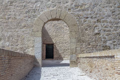 Access arch inside Santa Barbara castle. Horizontal view of access arch of stone and an ancient door in the background inside of Santa Barbara castle, alicante Stock Photo