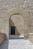 Access arch inside Santa Barbara castle. Vertical view of access arch of stone and an ancient door in the background inside of Santa Barbara castle, alicante Royalty Free Stock Images