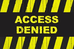 Access denied warning sign with yellow and black stripes painted over cracked wood. Royalty Free Stock Photo