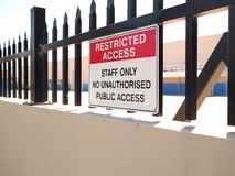 Access restricted sign on a steel fence tipped wall Stock Photo