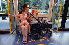Accessibility seat. GOLD COAST, AUS - NOV 04 2014:Mother travelling with a pram sit on accessibility seat in a tram.The space is secured for disabled people Royalty Free Stock Photo