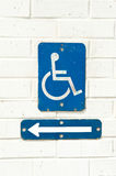 Accessibility sign. A handicap accessibility sign with direction arrow mounted on a white brick wall Stock Images