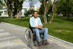 Free Accessible Environment For Disabled People Concept. Happy Black Guy In Wheelchair Going Down Ramp On City Street Stock Images - 220748134