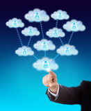 Accessing The Support Of Many Workers In The Cloud. Arm of a business man accessing the support of many knowledge workers. His index finger is touching a cloud royalty free stock images