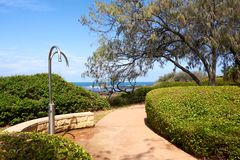 Accesso della spiaggia dalla via con le docce ed i giardini pubblici immagine stock libera da diritti