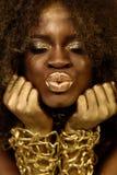 Accessoaries, состав и вьющиеся волосы золота очаровательной Афро-американской модели нося делая губы поцелуя, закрыли глаза Стоковые Фотографии RF