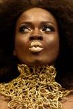 Accessoaries del oro del modelo que llevan afroamericano encantador, maquillaje y pelo rizado haciendo los labios del beso que mi Fotos de archivo