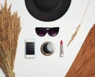Accessoire de mode, chapeau noir rond, lunettes de soleil, smartphone d'écran, miroir et rouge à lèvres rouge sur le fond blanc photos libres de droits