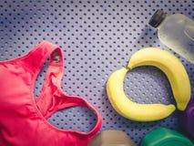 Accessoire de séance d'entraînement de gymnase des vêtements de sport roses, eau potable fraîche Images stock