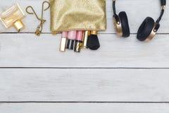 Accessoires, cosmétiques, parfums, écouteurs brillants se trouvant sur le bois photos stock