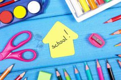 Accessoires d'école et de bureau avec la forme du bâtiment sur les conseils bleus, de nouveau au concept d'école Images libres de droits