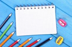 Accessoires d'école et de bureau avec le bloc-notes sur des conseils, de nouveau au concept d'école Images stock
