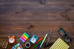 Accessoires d'étudiant Maquette de papeterie du ` s d'école ou d'étudiant avec des verres, réveil, carnet sur le fond en bois fon Photos stock
