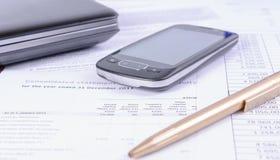 Accessoires d'affaires - un stylo, un téléphone et un ordinateur portable se trouvant sur des documents d'impôts photo libre de droits