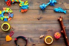 Accessoires d'animal familier Jouets près des cuvettes avec l'alimentation des animaux, collier sur l'espace en bois foncé de cop photo stock