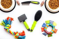 Accessoires d'animal familier pour le soin et la formation Brosses, jouets et nourriture sur la vue supérieure de fond blanc photos stock