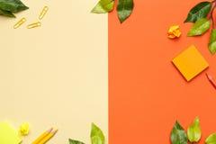 Accessoires de bureau avec des feuilles sur le fond jaune et orange Photo libre de droits